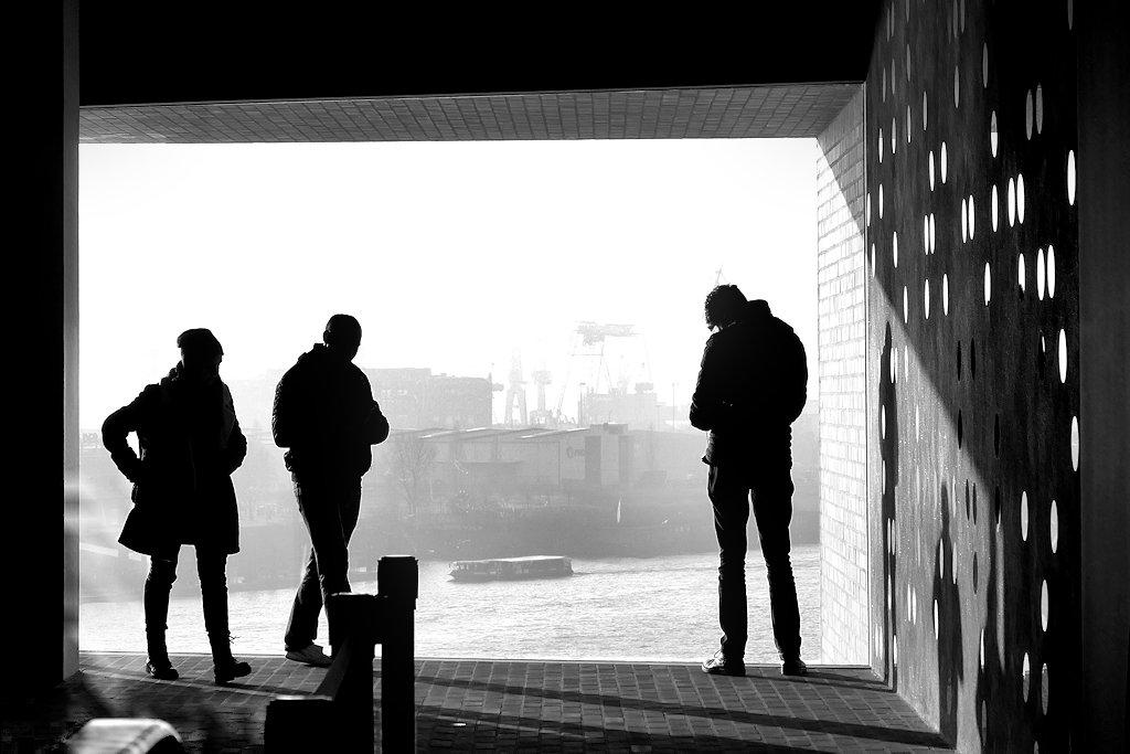Glasfront mit Ausblick in der Elbphilharmonie Hamburg im Gegenlicht mit Personen