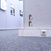 Vom Boden in die Ausstellung fotografiert mit Steckdose, Aufklebern und gerahmten Bildern
