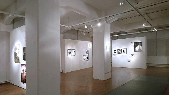 Hoher Raum mit zwei Säulen und weißen Wänden im Hintergrund, darauf gerahmte Bilder