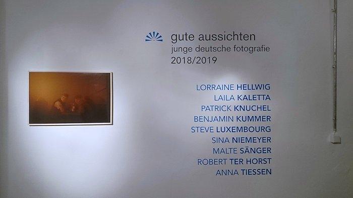 Auf einer Wand links Foto von zwei Jugendlichen im Kneipendunst, rechts Titel der Ausstellung und Namen der Künstler