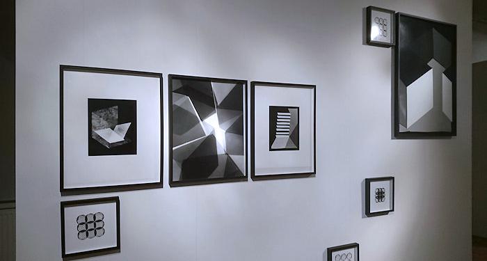weiße Wand mit quadratischenFotos nebeneinander und kleineren bunt verteilt