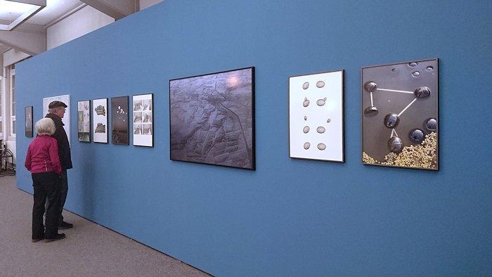 Zwei ältere Menschen schauen sich Fotos in verschiedenen Formaten auf einer blauen Wand an