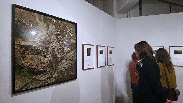 weiße Wand mit großen Luftbildfotos und rechteckigen Rahmen mit kleinen Fotos und Text