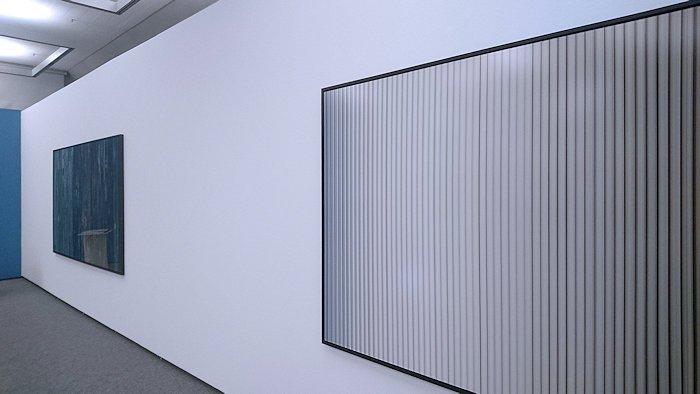 zwei großformatige, abstrakte Fotografien hänger an einer weißen Wand
