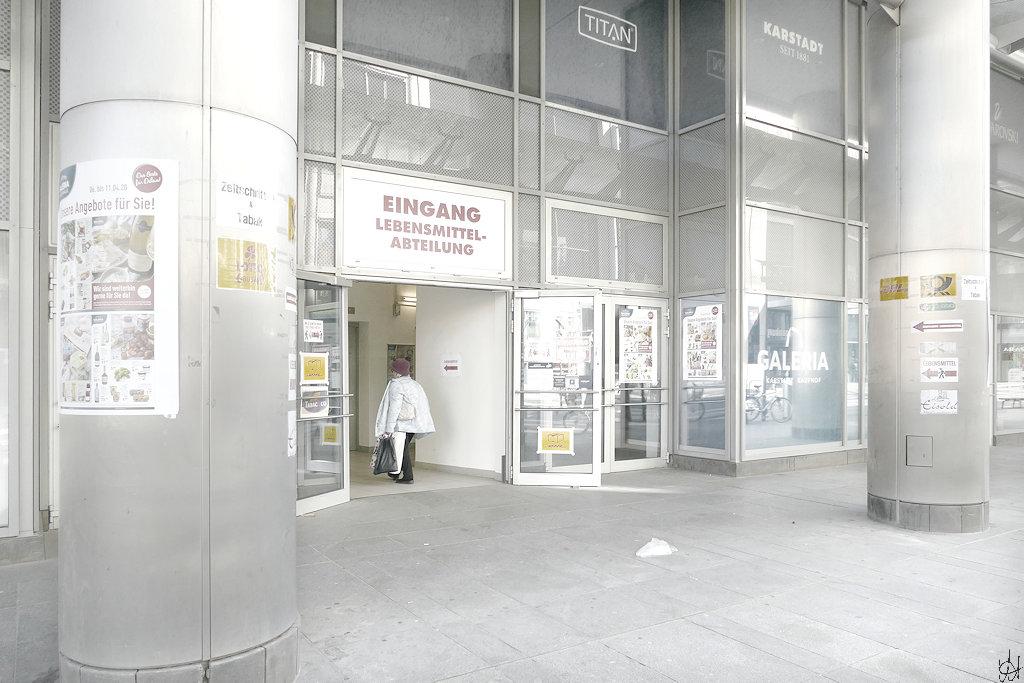 eine Frau besucht die Karstadt Lebensmittel-Abteilung duch den Noteingang