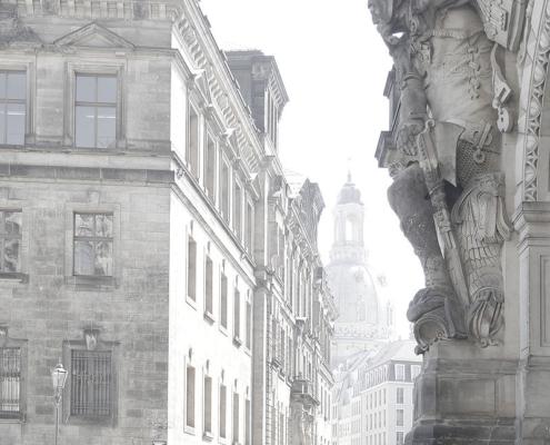 Rechts eine Figur am Georgentor, links das Ständehaus im Hintergrund die Dresdner Frauenkirche
