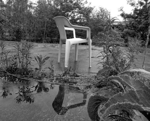 weißer Plastikstuhl am Wasser, Schwaz-Weiß Foto